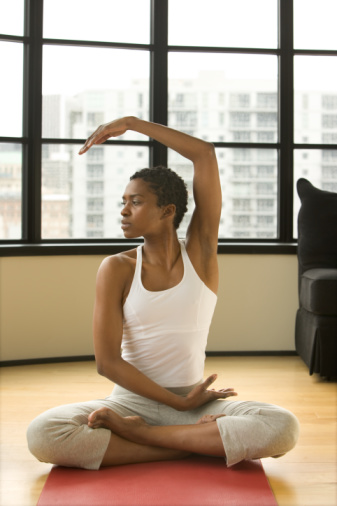 Young woman practicing yoga, sitting in lotus position, looking away